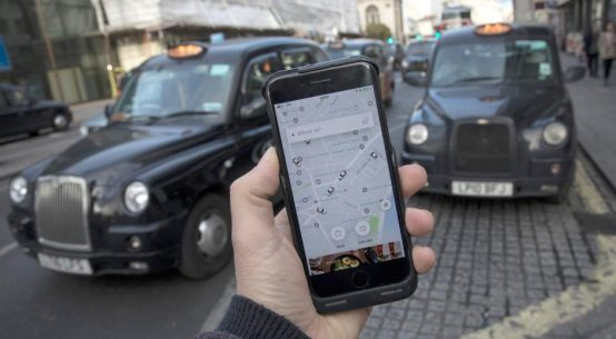 A photo illustration shows the Uber app on a mobile telephone, as it is held up for a posed photograph, with London Taxis in the background, in London, Britain November 10, 2017. REUTERS/Simon Dawson